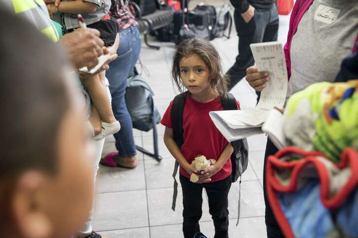 Cristi Mayen, 6, listens as her mother checks the bus tickets to their next destination, in Houston, July 26, 2018. After migrating here from Honduras, they were held for more than two weeks at a center in Dilley, Texas, before being released today. They said they were never separated and were en route to stay with family in North Carolina. (Scott Dalton/The New York Times)