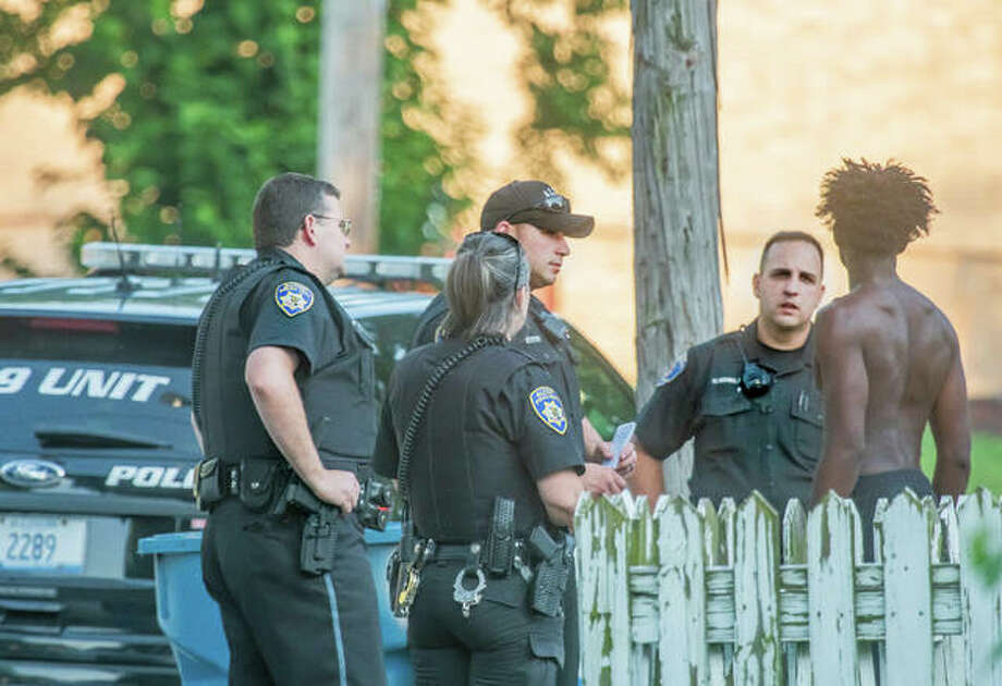 Alton police officers speak to a man in front of a home in the 1900 block of Washington Avenue Wednesday evening after the report of gunfire there.