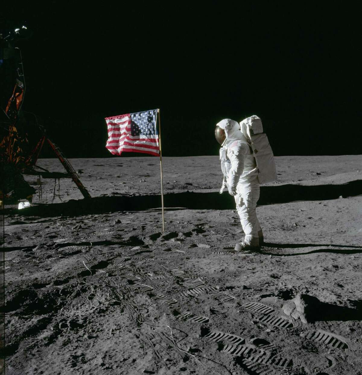 Astronaut Edwin E. Aldrin Jr., lunar module pilot of the first lunar landing mission, poses for a photograph beside the deployed United States flag during an Apollo 11 extravehicular activity (EVA) on the lunar surface. The Lunar Module (LM) is on the left, and the footprints of the astronauts are clearly visible in the soil of the moon. (NASA)