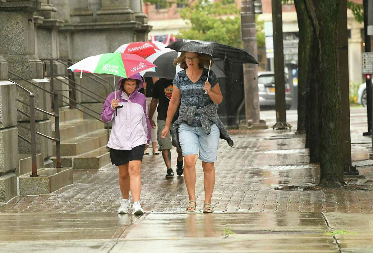 Pedestrians walk along Broadway near State St. with umbrellas during a downpour on Wednesday, Aug. 1, 2018 in Albany, N.Y. (Lori Van Buren/Times Union)