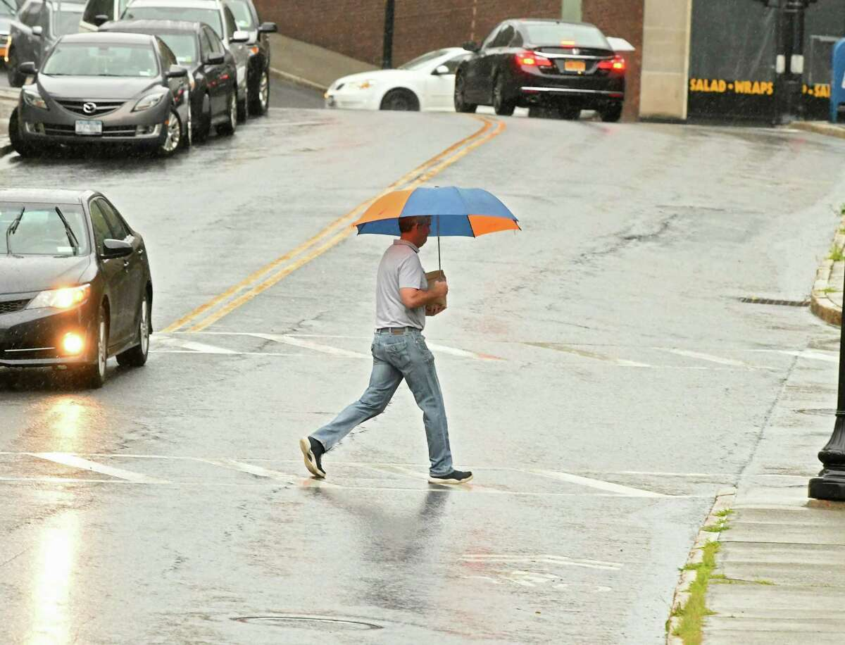 A pedestrian crosses Pine St. with an umbrella during a rainstorm on Wednesday, Aug. 1, 2018 in Albany, N.Y. (Lori Van Buren/Times Union)