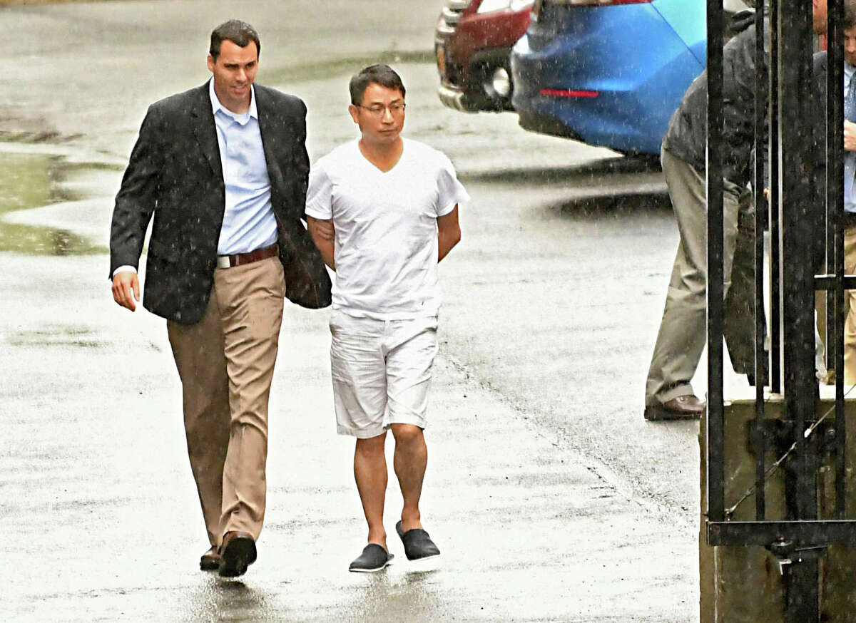 FBI agents escort Xiaoqing Zheng, principal engineer with GE's Power and Water division, into the rear entrance to the Federal Courthouse on Wednesday, Aug. 1, 2018 in Albany, N.Y. FBI agents raided his house at 8 Cephalonia Drive in Niskayuna on Wednesday morning. (Lori Van Buren/Times Union)