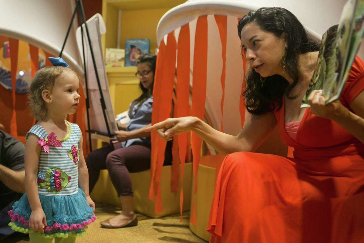 """Xelena Gonzlez, author of at """"All Around Us"""" points to a curious Ellory Goodreau, 2, as Gonzlez reads the book at The DoSeum July 7, 2018. """"All Around Us"""" has been honored with a notable children's book and the 2018 Texas Institute of Letters Literary Award for best picture book."""