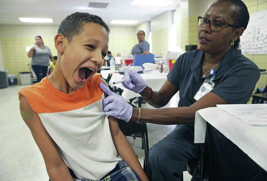 Despite early bravery, Micky Contreras recoils from the sting of a shot needle administered by LVN Pamela Long as kids get backpacks and bicycle helmets as well school supplies and vaccinations at the Garza Community Center back to school fair as on August 19, 2017. Photo: Tom Reel, Staff / San Antonio Express-News / 2017 SAN ANTONIO EXPRESS-NEWS