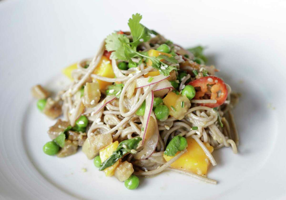 A soba noodle salad with mangoes, roasted eggplant, cilantro, peas, onion, basil, ginger and miso rice wine vinaigrette at Field & Tides restaurant, 705 E. 11th St. in the Heights.