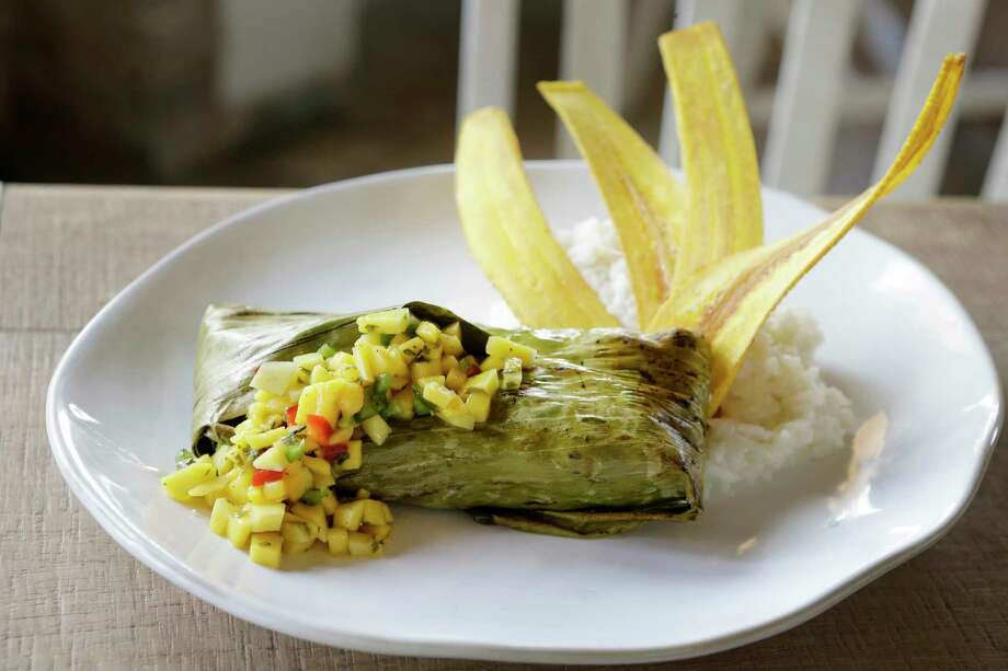 The banana leaf fish (fish of the day in banan leaf with curry, garlic and citrus served with mango salsa and fried plantains) is one of the new menu items at Field & Tides restaurant, 705 E. 11th St. in the Heights. Photo: Melissa Phillip, Houston Chronicle / © 2018 Houston Chronicle