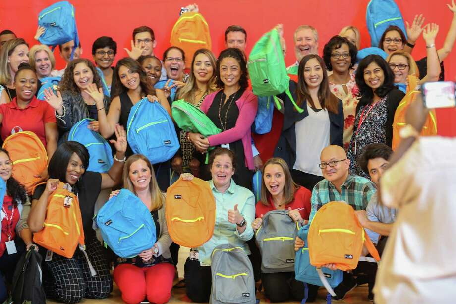 "Halliburton employees pose for a photo with some of the backpacks they packed at their headquarters Wednesday, Aug. 1, 2018, in Houston. Halliburton is exercising ""corporate social responsibility"" by doing a back-to-school giveaway. Photo: Steve Gonzales, Staff Photographer / Houston Chronicle / © 2018 Houston Chronicle"