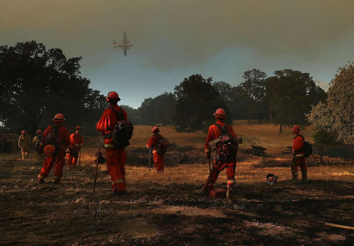 Inmate firefighters look on as a firefighting aircraft prepares to drop fire retardant ahead of the River Fire as it burns through a canyon on August 1, 2018 in Lakeport, California. The River Fire has burned over 27,000 acres, destroyed 7 homes and stands at 38 percent contained.