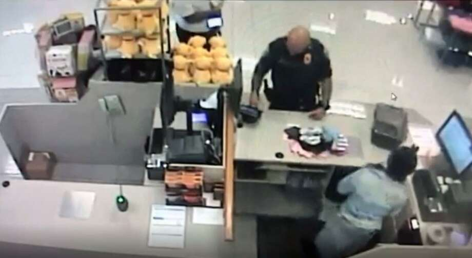 A screenshot from Kohl's surveillance video shows Sgt. Hector Irizarry paying for clothing a woman was allegedly stealing for her children on July 11.