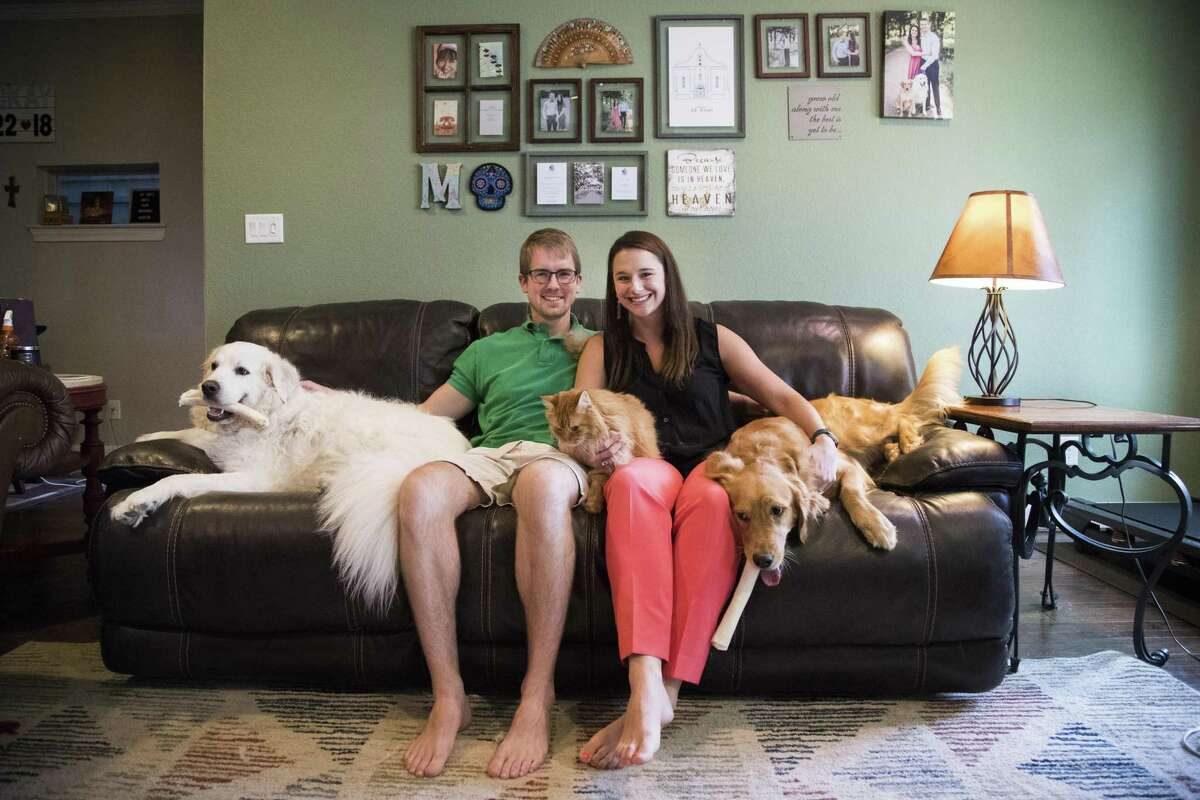Laura Palmer and her fiancé Alex Mackay sit in their living room with their pets Moose, Cora and Puff in Houston. The medical residents purchased their first home last year, before they made the leap to get engaged. ( Marie D. De Jesús / Houston Chronicle )