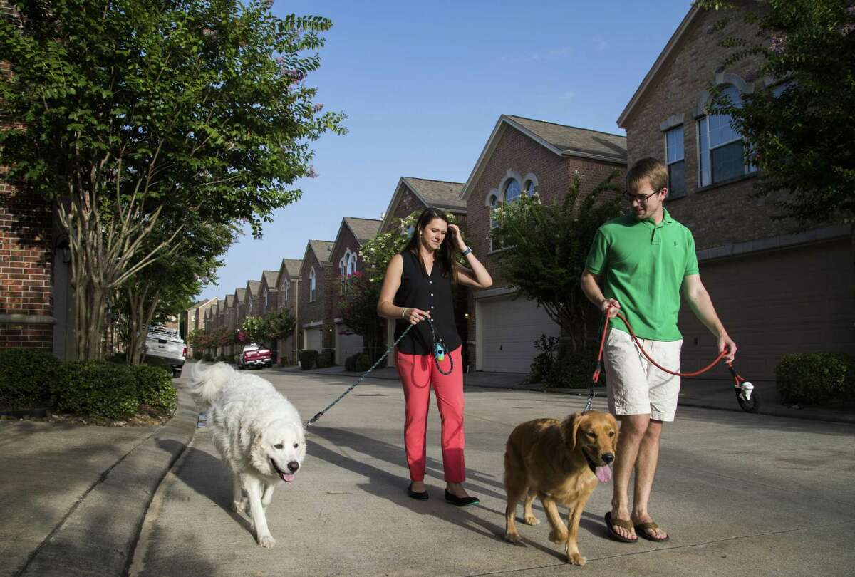 Laura Palmer and her fiancé Alex Mackay walk their pets Moose and Cora in their neighborhood in Houston. Before tying the knot, the couple decided that financially it was smart to purchase their home instead of paying rent and home ownership has allowed them to own pets. ( Marie D. De Jesús / Houston Chronicle )