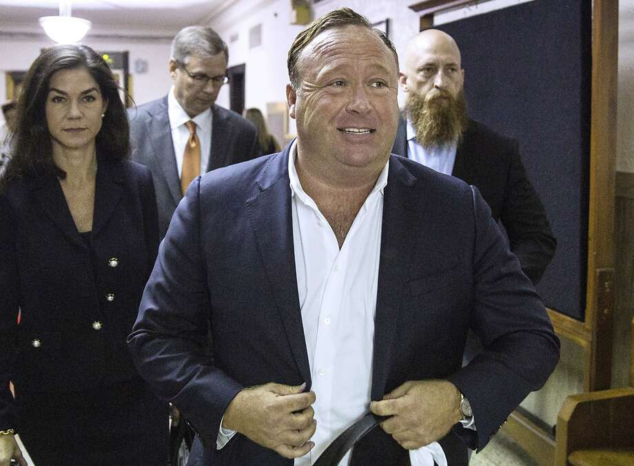 "FILE - In this April 17, 2017, file photo, ""Infowars"" host Alex Jones arrives at the Travis County Courthouse in Austin, Texas. Jones filed a motion Friday, July 20, 2018, to dismiss a defamation lawsuit filed by families of some of the 26 people killed in the 2012 Sandy Hook school shooting in Newtown, Conn. The music streaming service Spotify says it has removed some episodes of ""The Alex Jones Show"" podcast for violating its hate content policy. The company said late Wednesday that it takes reports of hate content seriously and reviews any podcast or song reported by customers. (Tamir Kalifa/Austin American-Statesman via AP, File) Photo: Tamir Kalifa, Associated Press"