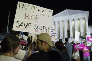 FILE - In this July 9, 2018 file photo, demonstrators holds signs as they gather in front of the Supreme Court in Washington after President Donald Trump announced Judge Brett Kavanaugh as his Supreme Court nominee. Worried by the prospect of a reconfigured court, abortion-rights advocates are intensifying efforts to ensure access to abortion for women who might be affected by a new wave of bans and restrictions. (AP Photo/Cliff Owen, File)