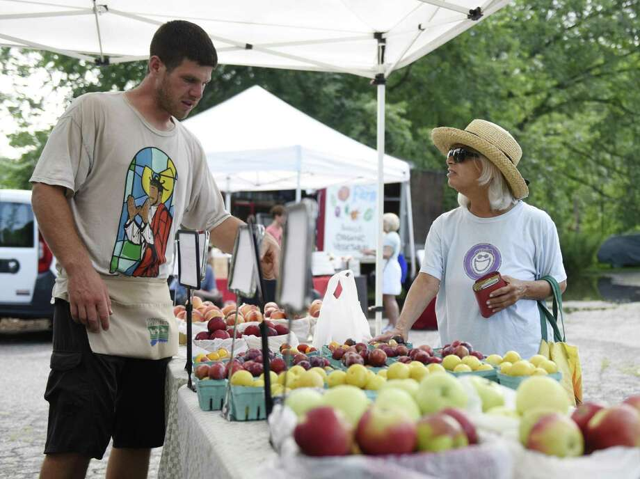 Riverside's Debra Feldman buys fruit from Woodland Farms' Jesse Teveris at the Old Greenwich Farmers' Market at Living Hope Community Church in Old Greenwich, Conn. Wednesday, Aug. 1, 2018. More than a dozen vendors offer fresh produce, baked goods, meat, soups, jams, pasta, flowers, and more. The market, which also features live music, occurs every Wednesday afternoon rain or shine through November. Photo: Tyler Sizemore / Hearst Connecticut Media / Greenwich Time