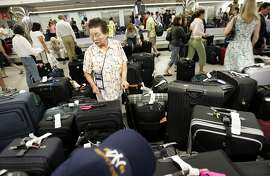 **ADVANCE FOR USE WEEKEND AUG. 30-31, AND THEREAFTER** FILE ** In this June 28, 2007 file photo, passengers look for luggage at American Airlines baggage claim at LaGuardia Airport in New York. The grip U.S. airlines have on travelers' wallets is about to get tighter as carriers cut more domestic capacity starting in September, 2008, due to the high cost of fuel. (AP Photo/Rob Carr, file)