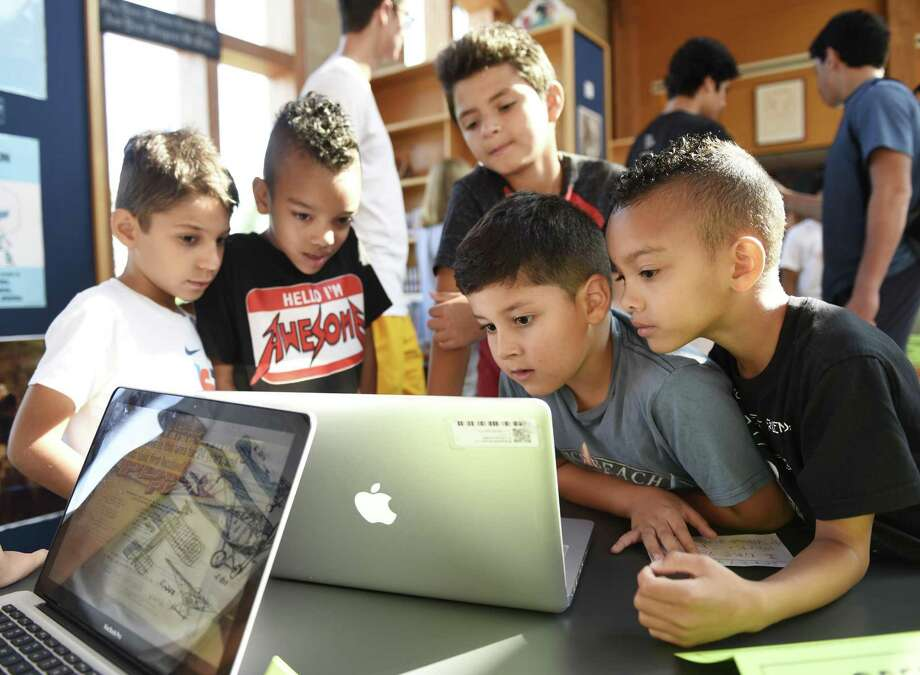 Rising second graders, from row from left, Leandro Locatelli DeCosta, Julius Hill, Jeffrey Villeda, and Hendrix Hill, look at the Greenwich Police photojournalism project by rising sixth grader Jacob Fajardo, back row, at the Brunswick Horizons photojournalism project showcase at Brunswick Lower School on the King Street campus in Greenwich, Conn. Thursday, Aug. 2, 2018. Rising sixth graders spent time observing and photographing local businesses and town establishments to learn communication and photography skills while gaining a sense of community. First graders and special guests were invited to see students' projects in a showcase Thursday morning. Photo: Tyler Sizemore / Hearst Connecticut Media / Greenwich Time
