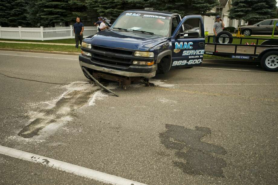 A towing service works to remove a vehicle from the scene of a collision at Wackerly and Elliott on Thursday, Aug. 2, 2018 in Midland. (Katy Kildee/kkildee@mdn.net) Photo: (Katy Kildee/kkildee@mdn.net)