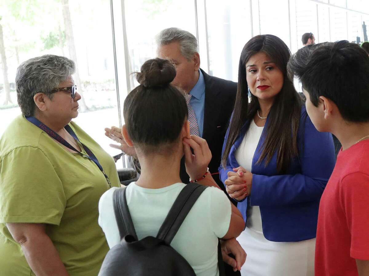 Houston ISD Trustees Elizabeth Santos, second from right, and Dr. Sergio Lira, rear-center, talk with Juan Hernandez, 11, right, Delanie Perez, 11, front-center, both HISD students, and their former fifth-grade teacher, Lucia Moreno, left, before a press conference at Hattie Mae White Educational Support Center, Thursday, Aug. 2, 2018, in Houston.