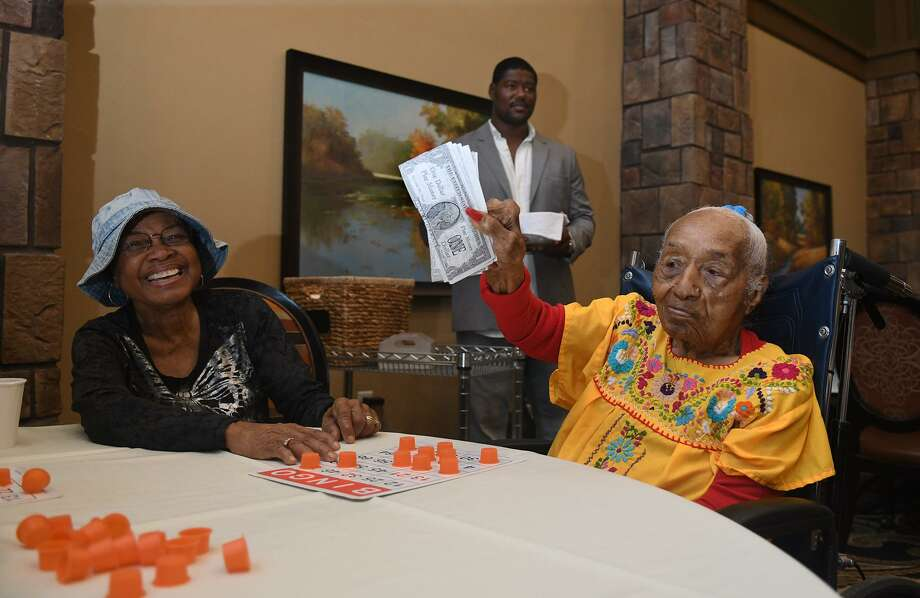 Georgia Mitchell, 104, right, much to the delight of her daughter Bernice Satterwhite, shows off her prize after winning the first round of bingo, called by NFL player Laurence Gibson, center, at Landon Ridge - Kingwood on August 1, 2018. Photo: Jerry Baker, Contributor / Houston Chronicle / Houston Chronicle