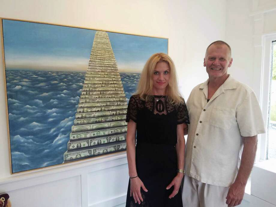 "Oksana Tanasiv and Mark Krueger in front of one of the artworks in the ""Dollar Art"" series at the X.po.zur Gallery in Westport. Photo: Contributed Photo"