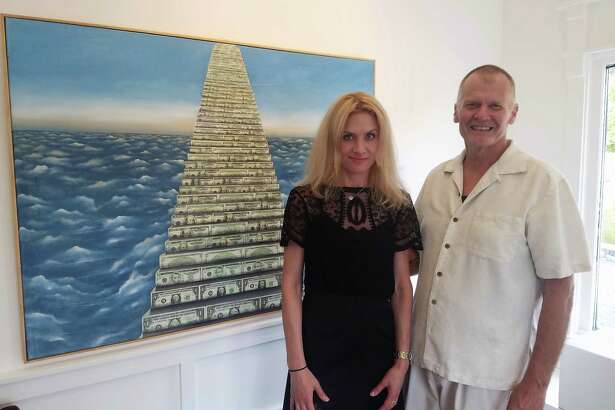 """Oksana Tanasiv and Mark Krueger in front of one of the artworks in the """"Dollar Art"""" series at the X.po.zur Gallery in Westport."""
