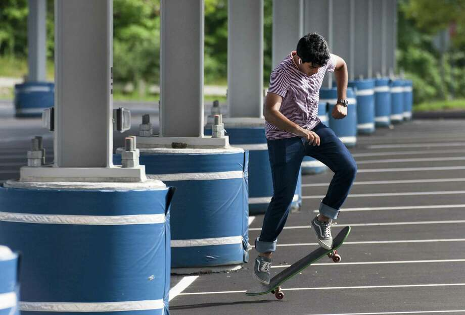 Rohan Butani, of Fairfield, spends some time practicing his skateboarding skills in the parking lot at Fairfield Ludlowe High School on July 27. Photo: Christian Abraham / Hearst Connecticut Media / Connecticut Post