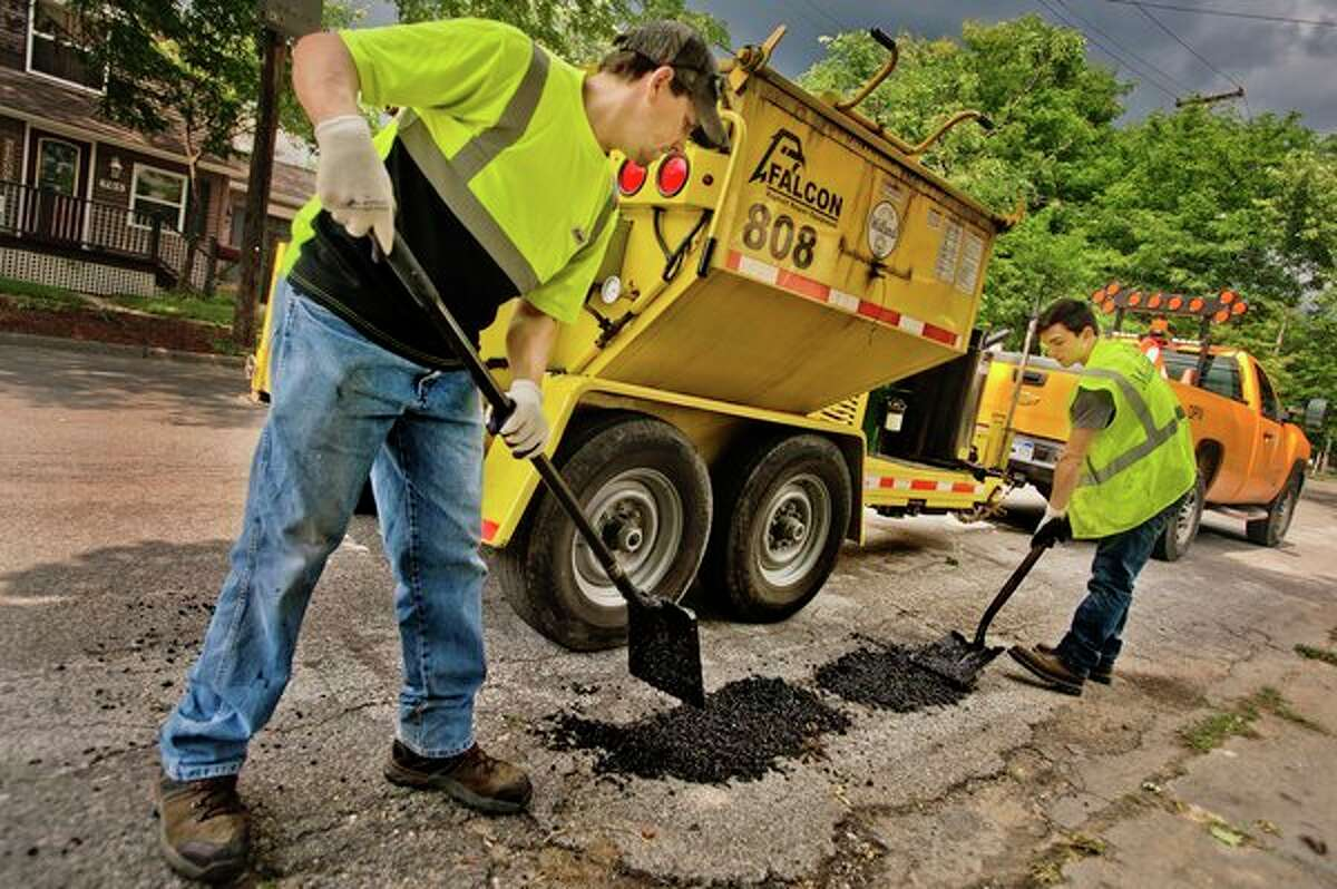 City of Midland employees Roy Saxton, left, and Blake Albee fill potholes on State Street near Pine on Thursday afternoon. The Aug. 7 Primary ballot will ask Midland County voters to decide on a 1.0 millage renewal for roads. (Katy Kildee/kkildee@mdn.net)