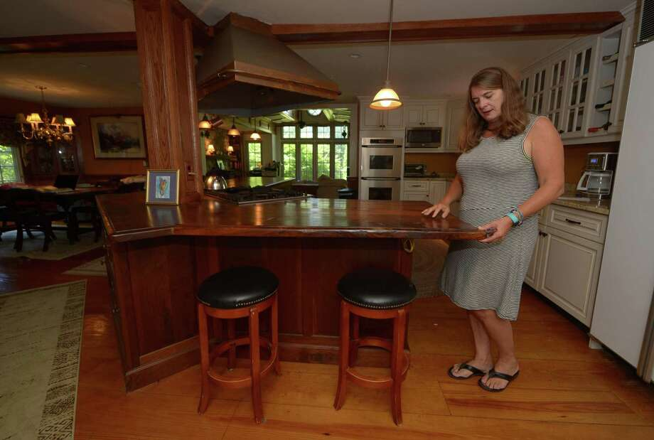 Lisa Wilson Grant talks about the countertop and cabinetry she had made from an old tree at her home at Tuesday, July 31, 2018, at 377 Highland Ave. in Norwalk, Conn. Grant has written a history of Norwalk, and what she learned about the journey includes the tale of her own home which was altered to the Tudor style it is today by Harry Stacey Benton, a fine artist famous for his Cream of Wheat ads and one of the first guild artists at the Silvermine Arts Center. Photo: Erik Trautmann / Hearst Connecticut Media / Norwalk Hour