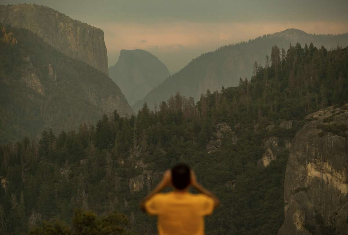 Francisco Avendano, visiting from Madrid, Spain, photographs Half Dome as smoke from the Ferguson Fire hangs over Yosemite National Park, Calif., on Tuesday, July 24, 2018. Parts of the park, including Yosemite Valley, will close Wednesday as firefighters work to contain the blaze. (AP Photo/Noah Berger)
