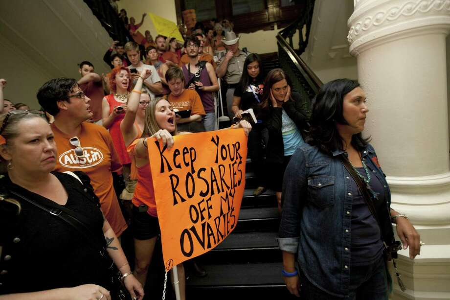 Abortion rights advocates protest in the State Capitol in 2013 as anti-abortion rights supporters pass them in Austin, Texas. One objection to a law passed last year that requires fetal remains be buried or cremated is that this imposes one religious belief on others. Photo: Tamir Kalifa /AP / FR170773 AP