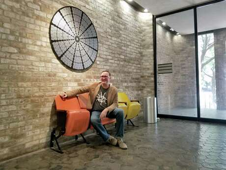 James Glassman, sits on Astrodome seats in the foyer of the Hansen Partners' office on Richmond Avenue. He is wearing a t-shirt showing the Loop 610 and above him hangs an aluminum ceiling sheet modeled after the Astrodome ceiling.