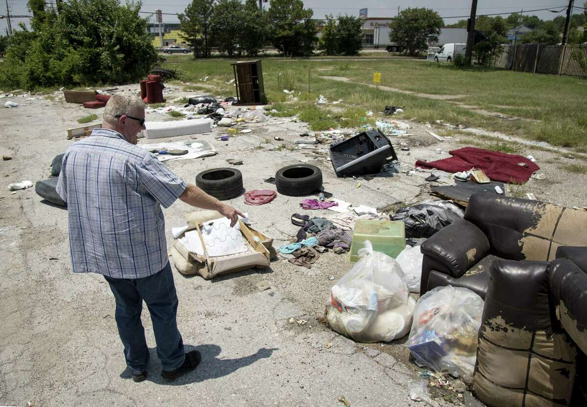 Randy Scales, a lieutenant with the Harris County Constable Precinct 1, surveys an illegal dump site in north Houston, Thursday, July 26, 2018, in Houston.