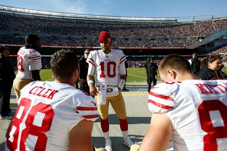 Jimmy Garoppolo  10 of the San Francisco 49ers talks on the sideline with  Garrett Celek 88fda6485