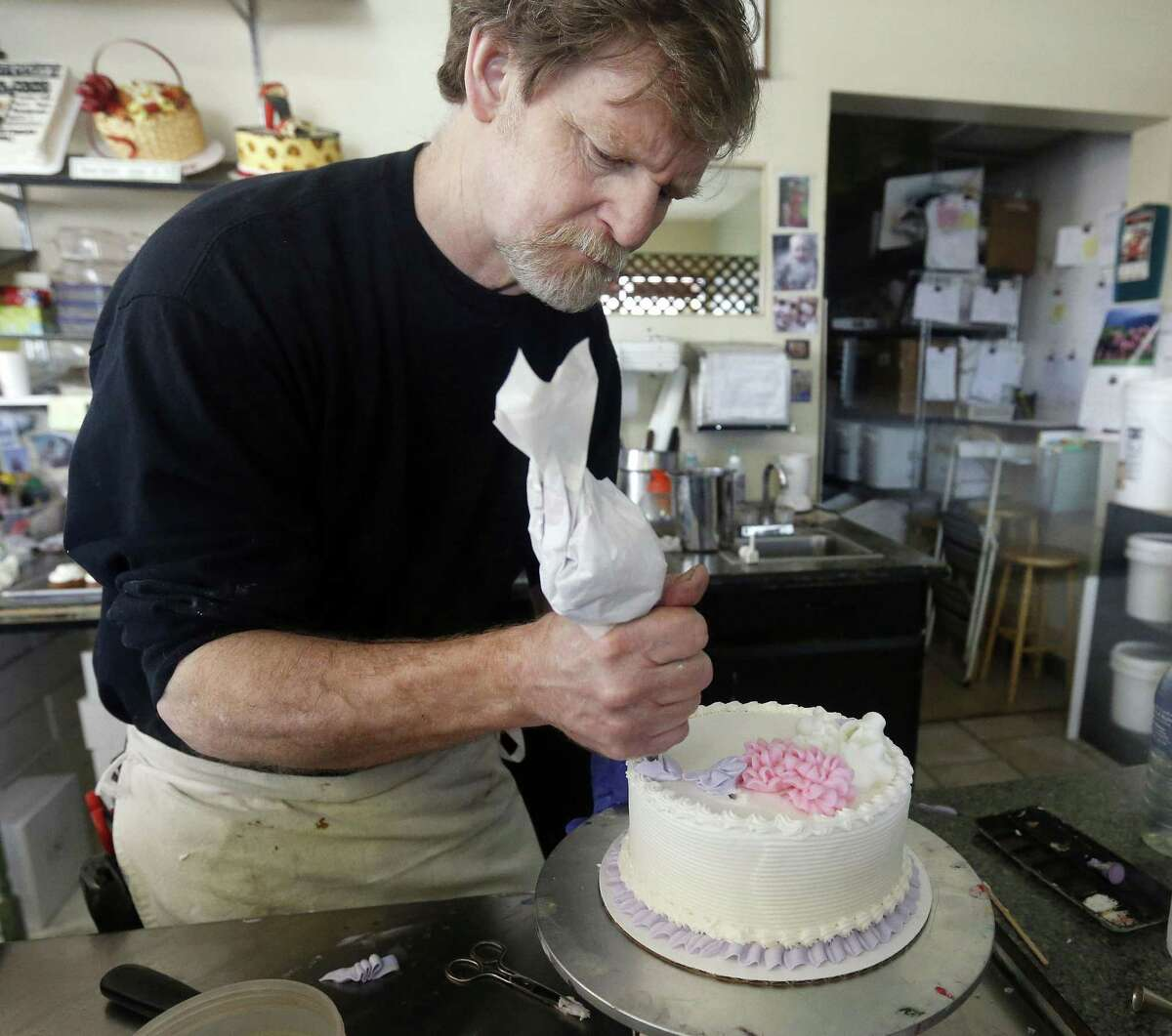 In this March 10, 2014, file photo, Masterpiece Cakeshop owner Jack Phillips decorates a cake inside his store in Lakewood, Colo. Prominent chefs, bakers and restaurant owners want the Supreme Court to rule against a Colorado baker who wouldnt make a cake for a same-sex couples wedding. The food makers say that once they open their doors for business, they dont get to choose their customers.