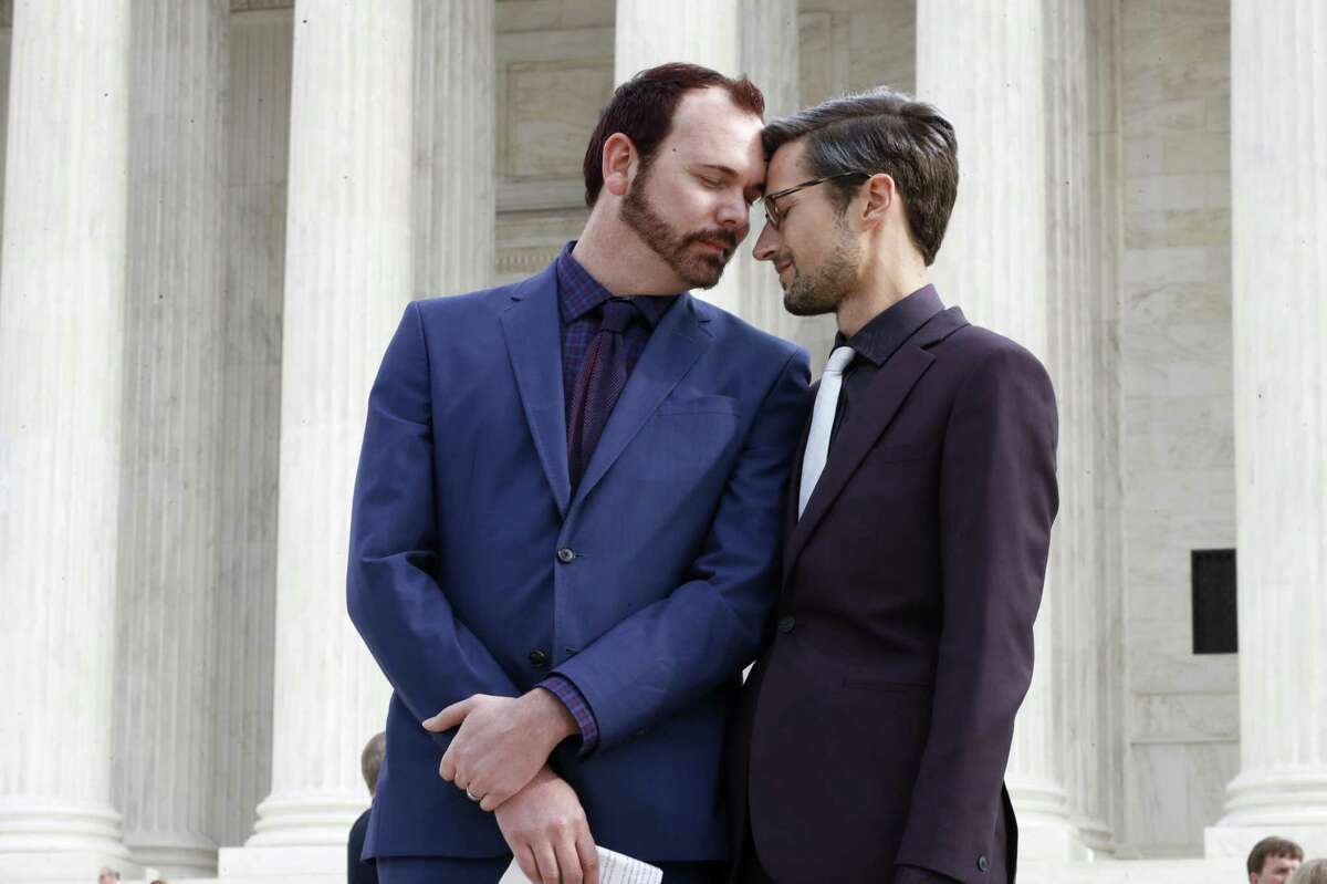 In this Dec. 5, 2017 file photo, Charlie Craig, left, and David Mullins touch foreheads after leaving the Supreme Court in Washington. The Supreme Court is setting aside a Colorado court ruling against a baker who wouldnt make a wedding cake for a same-sex couple. But the court is not deciding the big issue in the case, whether a business can refuse to serve gay and lesbian people.
