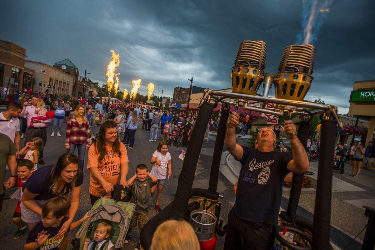 "Jason Guilici of Midland, right, turns on the burners inside a hot air balloon during the Midland Balloon Festival's annual ""Main Street Glow"" event on Thursday, Aug. 2, 2018. (Katy Kildee/kkildee@mdn.net)"
