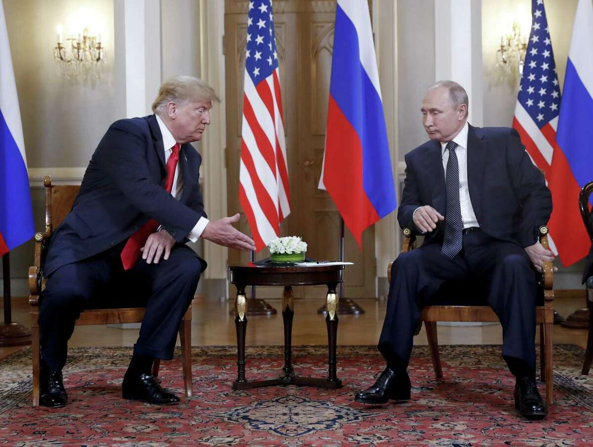 U.S. President Donald Trump, left, extends his hand to Russian President Vladimir Putin, right, at the beginning of a meeting at the Presidential Palace in Helsinki, Finland, Monday, July 16, 2018.