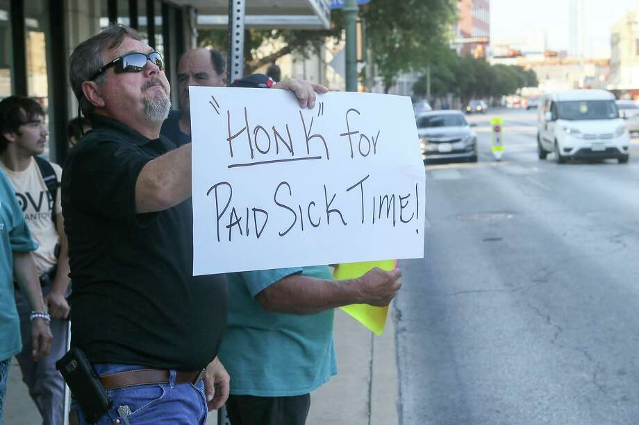 "Rick Sisk holds up a ""'Honk' for Paid Sick Time!"" sign to passing cars as members of Working Texans for Paid Sick Time rally in front of City Hall, Aug. 2, 2018. A reader warns business owners to read up on the legislation effective Aug. 1 to protect their businesses. Photo: Marvin Pfeiffer /San Antonio Express-News / Express-News 2018"