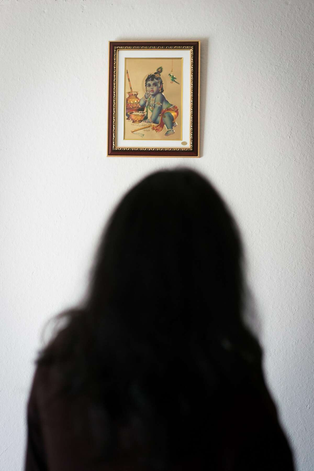A woman, who chooses to remain anonymous, looks at a photo of a Hindu god inside of her home in Fremont, Calif. on Friday, June 29, 2018. The woman known as