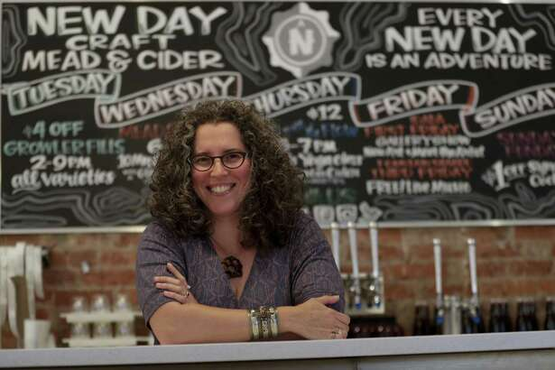 """Tia Agnew, co-founder and CEO of New Day Craft, an Indianapolis-based producer of mead and cider, poses in the tasting room in Indianapolis, Monday, July 30, 2018. Agnew said she was excited to put up her """"Open to All"""" window sticker, which she says matches her """"personal and professional ethos."""" She's not worried that it will be a turn-off to some potential patrons."""