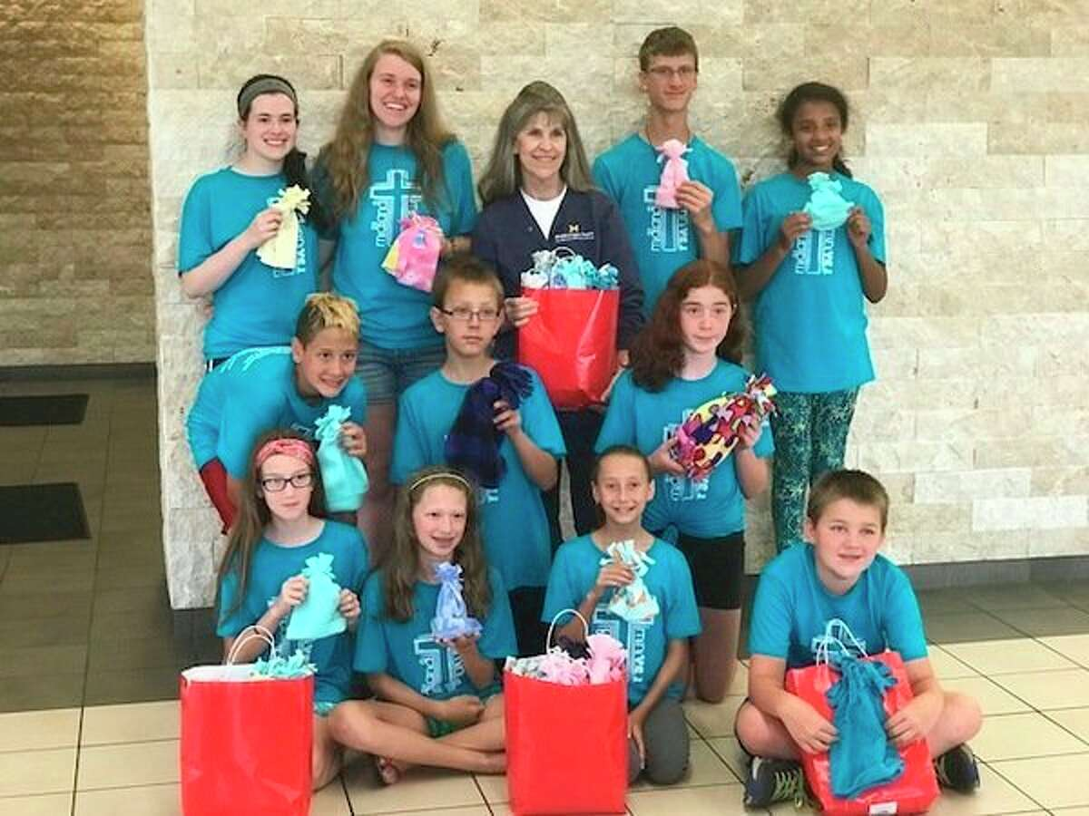 Local students deliverabout 100 baby hats for infants and toddlers receiving care at MidMichigan Medical Center - Midland. Shown delivering the baby hats are: Top row, from left, Maddy, Elizabeth, Kathy Amble, R.N., MidMichigan Medical Center - Midland, Chris and Tianna.Middle row, from left, Aaron, William and Claire. Front row, from left: Isabel, Cheryl, Faith and Sean. (Photo provided)