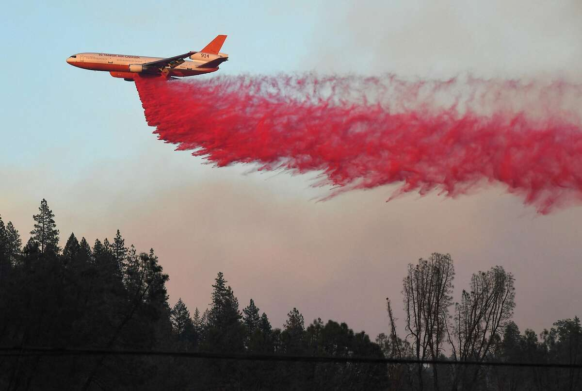 """An air tanker drops fire retardent to try to contain flames from the Carr fire as it spreads towards the town of Lewiston near Redding, California, on August 2, 2018. Thousands of firefighters were struggling on August 2 to contain two vast wildfires in California, one of which has become one of the most destructive blazes in the state's history. The Carr Fire has scorched 126,00 acres (51,00 hectares) of land since July 23, when authorities say it was triggered by the """"mechanical failure of a vehicle"""" that caused sparks to fly in tinderbox dry conditions."""