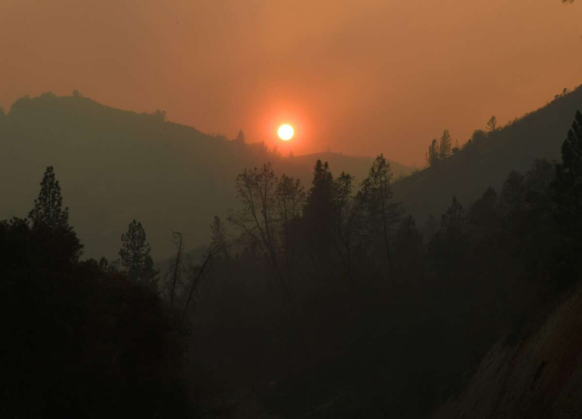 """The sun sets over an area partially burnt by the Carr fire as it spreads towards the town of Lewiston near Redding, California, on Auigust 2, 2018. Thousands of firefighters were struggling on August 2 to contain two vast wildfires in California, one of which has become one of the most destructive blazes in the state's history. The Carr Fire has scorched 126,00 acres (51,00 hectares) of land since July 23, when authorities say it was triggered by the """"mechanical failure of a vehicle"""" that caused sparks to fly in tinderbox dry conditions."""