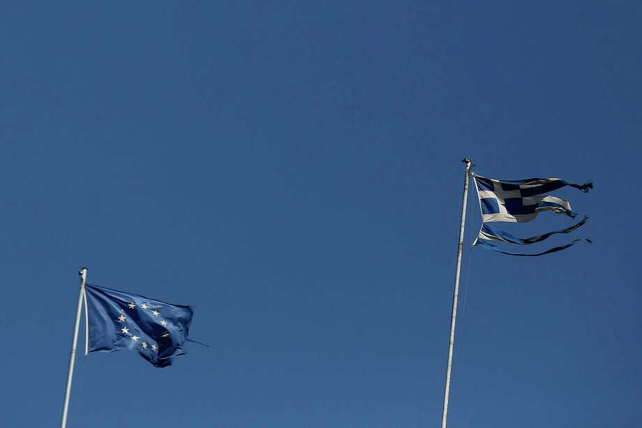 A tattered Greek national flag, right, flies beside a European Union flag on the roof of a building in Athens on July 21, 2015. Photo: Yorgos Karahalis/Bloomberg / Bloomberg