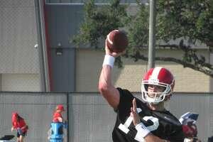 Quinten Dormady (12) goes through quarterback drills Friday.
