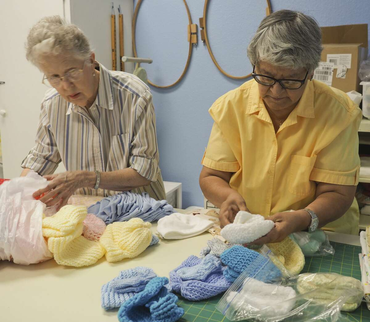 Pat Stevens and Lucy Melgoza sort some of the knitted items to be packaged together for delivery to Midland Memorial Hospital for newborns. 07/27/18 Tim Fischer/Reporter-Telegram