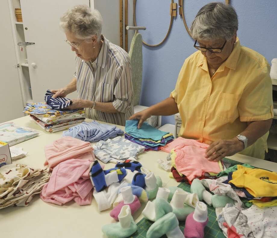 Pat Stevens and Lucy Melgoza sort some of the knitted items to be packaged together for delivery to Midland Memorial Hospital for newborns. 07/27/18  Tim Fischer/Reporter-Telegram Photo: Tim Fischer/Midland Reporter-Telegram