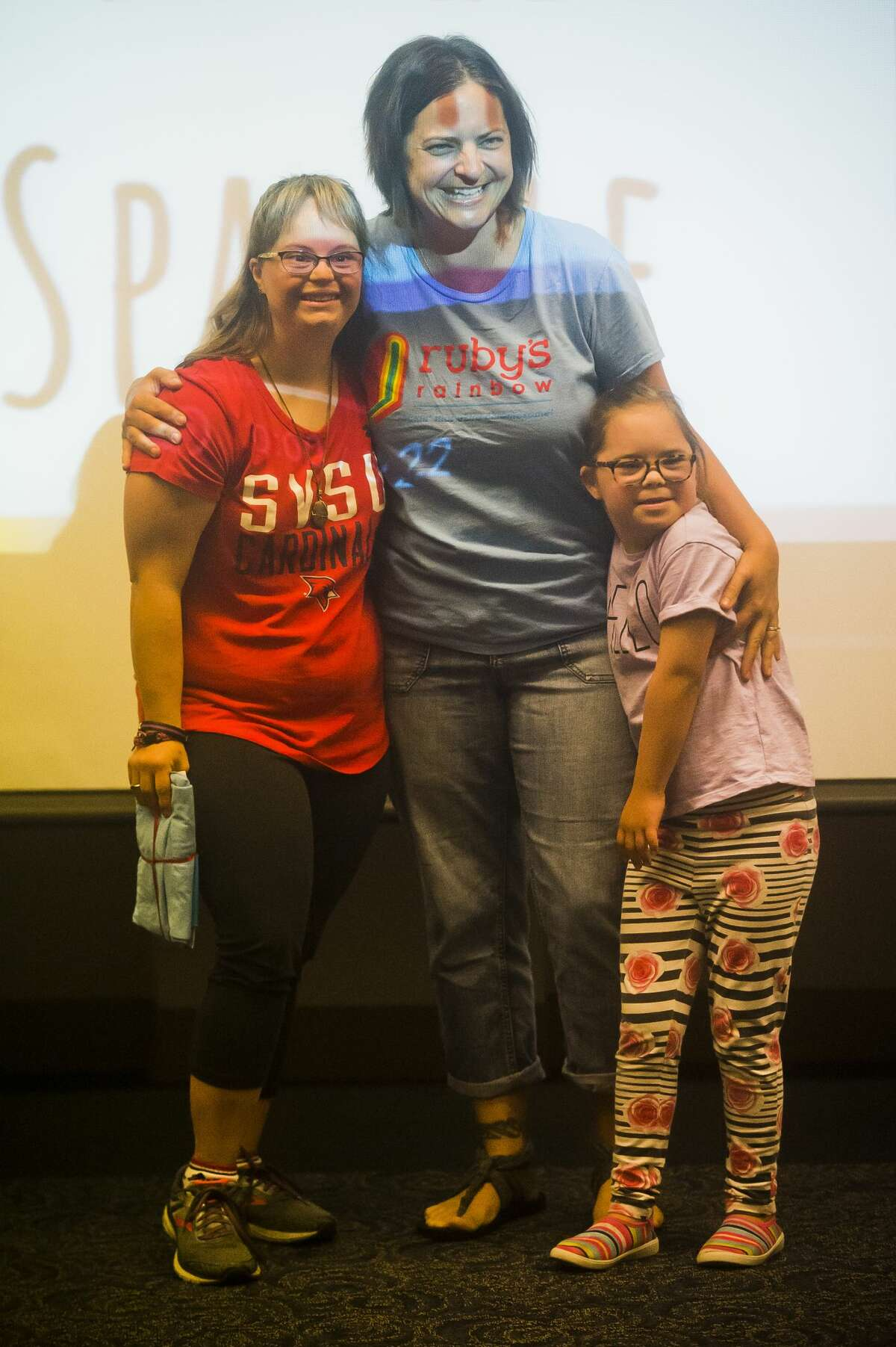 Jessica Day poses for a photo with Liz Plachta, center, and Ruby Plachta, right, after walking into a surprise celebration during which Day was told she is receiving the Ruby's Rainbow Scholarship on Friday, Aug. 3, 2018 at Saginaw Valley State University. Ruby's Rainbow provides scholarships for adults with Down Syndrome who have dreams of pursuing higher education. (Katy Kildee/kkildee@mdn.net)