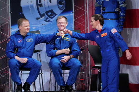 Astronauts Nicole Mann, right, and Eric Boe, left, bump fists in front of Christopher Ferguson after being introduced during a NASA event to announce the astronauts assigned to crew the first flight tests and missions of the Boeing CST-100 Starliner and SpaceX Crew Dragon, Friday, Aug. 3, 2018, in Houston. The astronauts will ride the first commercial capsules into orbit next year and return human launches to the U.S. (AP Photo/David J. Phillip)