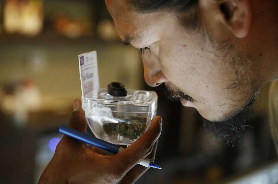 Paul Whiterock smells marijuana for sale July 30 in Las Vegas. Tax revenue for the first year of sales should be $70 million. Photo: John Locher / Associated Press